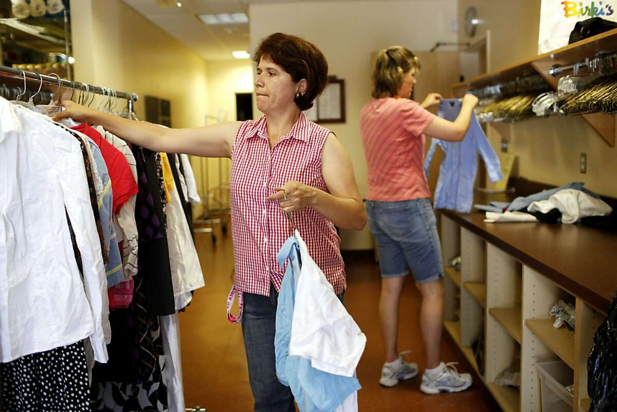 Volunteers Jaqueline Rueda (left) and Tricia Costantini sort through donated clothing at St. Francis Center on Wednesday, September 21, 2011 in Redwood City, Calif. The center gives out 25,000 bags of clothing a year.
