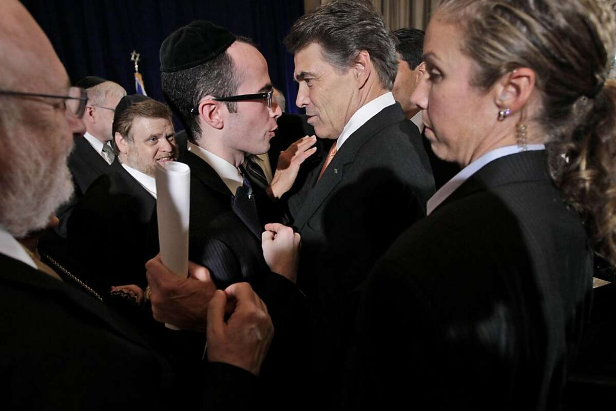 Republican presidential candidate, Texas Gov. Rick Perry, center is surrounded by security, right, and supporters after a news conference, Tuesday, Sept. 20, 2011, in New York. (AP Photo/Mary Altaffer)