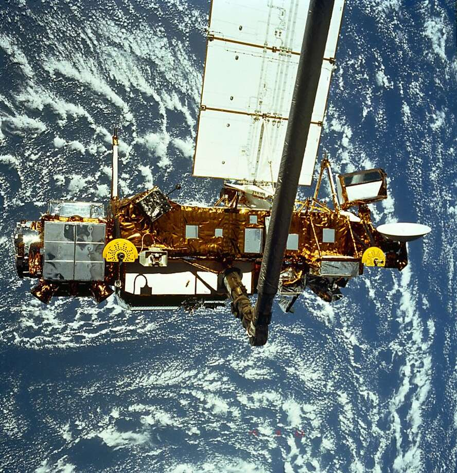 """This September 12, 1991 NASA handout shows an STS-48 onboard photo of the Upper Atmosphere Research Satellite (UARS) in the grasp of the RMS (Remote Manipulator System) during deployment. Originally designed for a three-year mission, UARS measured chemical compounds found in the ozone layer, wind and temperature in the stratosphere, as well as the energy input from the sun. Together, these measurements helped define the role of Earth's upper atmosphere in climate and climate variability. The 35-foot-long, 15-foot-diameter UARS, decommissioned on December 14, 2005, is expected to re-enter Earth's atmosphere in late September or early October 2011, almost six years after the end of a productive scientific life. Although the spacecraft will break into pieces during re-entry, not all of it will burn up in the atmosphere. The risk to public safety or property is extremely small, and safety is NASA's top priority. Since the beginning of the Space Age in the late-1950s, there have been no confirmed reports of an injury resulting from re-entering space objects. AFP PHOTO / HO / NASA      = RESTRICTED TO EDITORIAL USE - MANDATORY CREDIT """"AFP PHOTO / NASA  """" - NO MARKETING NO ADVERTISING CAMPAIGNS - DISTRIBUTED AS A SERVICE TO CLIENTS = (Photo credit should read HO/AFP/Getty Images) Photo: Ho, AFP/Getty Images"""