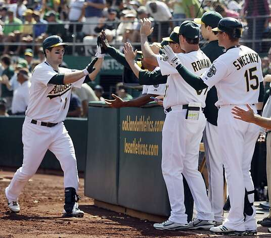 Oakland Athletics' Josh Willingham, left, is high-fived by teammates after his solo home run against the Los Angeles Angels during the third inning of a baseball game in Oakland, Calif.,  Wednesday, Sept. 14, 2011. (AP Photo/Marcio Jose Sanchez) Photo: Marcio Jose Sanchez, AP