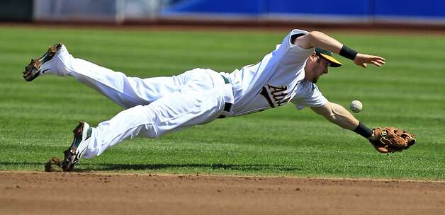 Oakland Athletics second baseman Eric Sogard makes a diving attempt at ground ball hit by Los Angeles Angels' Vernon Wells during the second inning of a baseball game in Oakland, Calif.,  Wednesday, Sept. 14, 2011. Wells got a single on the play (AP Photo/Marcio Jose Sanchez) Photo: Marcio Jose Sanchez, AP