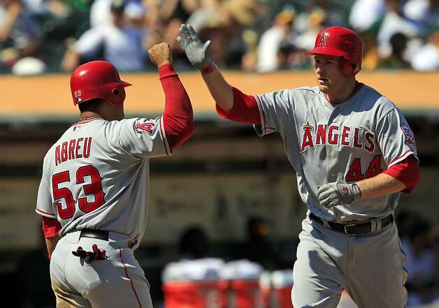 Los Angeles Angels' Mark Trumbo, right, celebrates with teammate Bobby Abreu after hitting a two-run home run against the Oakland Athletics during the sixth inning of a baseball game in Oakland, Calif., Wednesday, Sept. 14, 2011. (AP Photo/Marcio Jose Sanchez) Photo: Marcio Jose Sanchez, AP