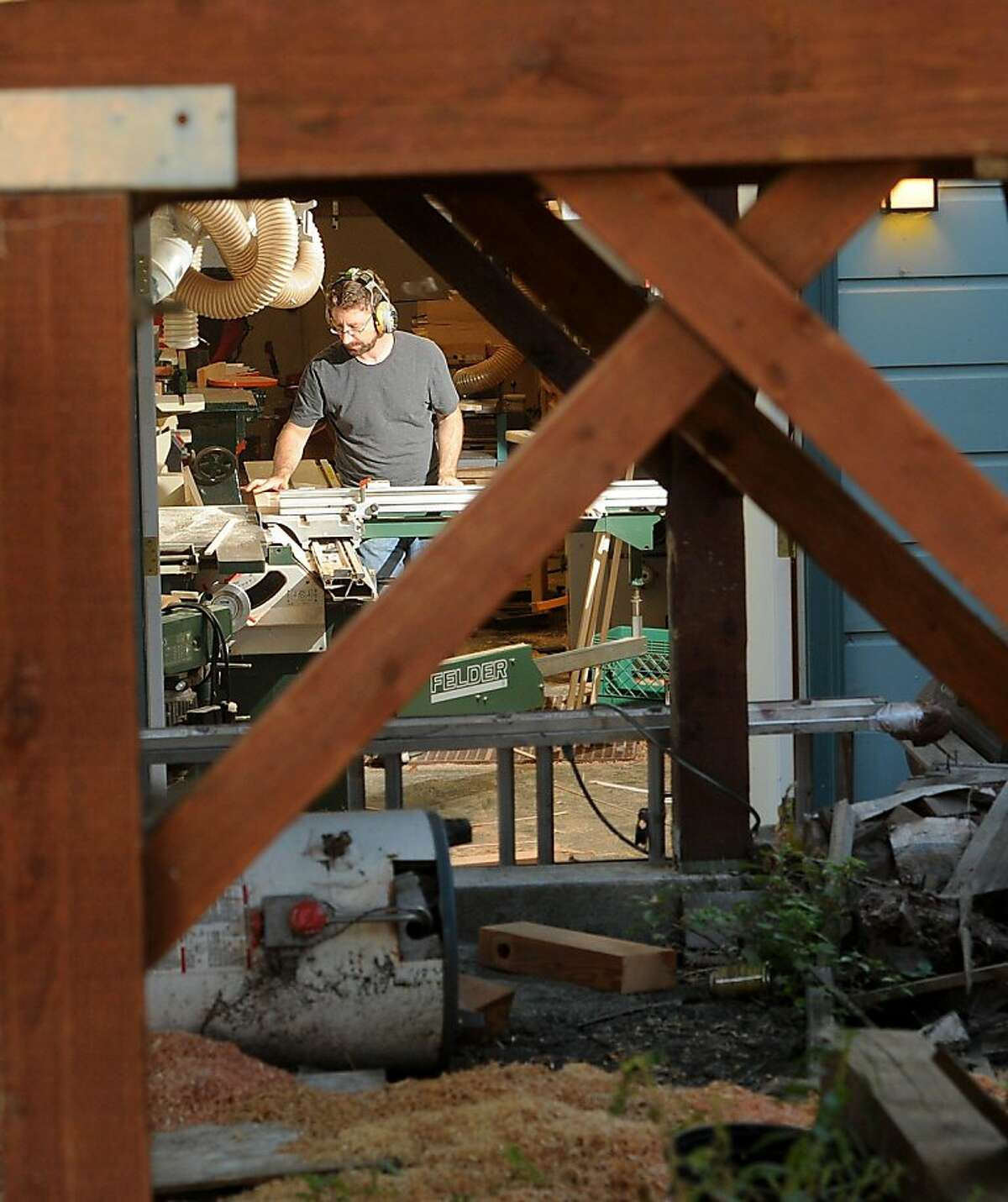 Joe Russack uses a basement workshop to build cabinets for his Oakland, Calif., home on Friday, Sept. 16, 2011. Russack intended to remodel his home by himself, but ended up hiring contractors after the city's Building Services department demanded fines for the blighted property.
