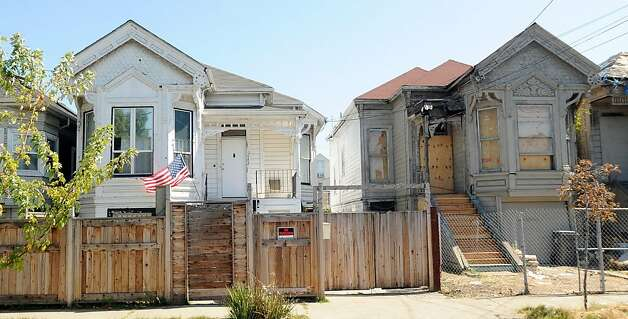 Michelle Cassens' Oakland, Calif., house, left, stands next to a derelict property on Friday, Sept. 16, 2011. Photo: Noah Berger, Special To The Chronicle