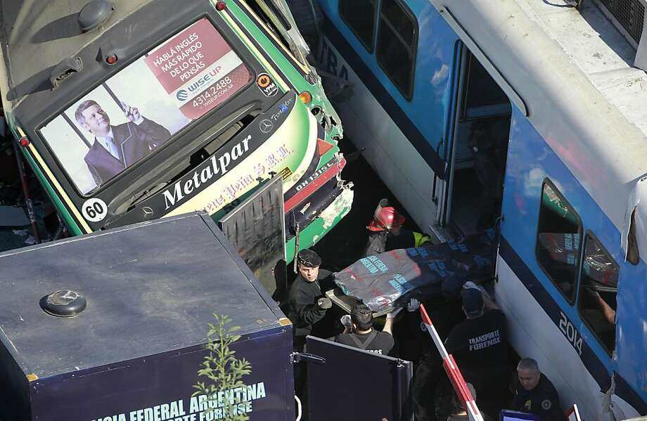 Police retrieve the body of a train crash victim in Buenos Aires, Argentina, Tuesday, Sept. 13, 2011. At least seven people were killed and 162 injured in a rush-hour crash involving two trains and a bus whose driver drove around barriers in an attempt to beat them across the tracks, Argentine authorities said. (AP Photo/Victor R. Caivano) Photo: Victor R. Caivano, AP