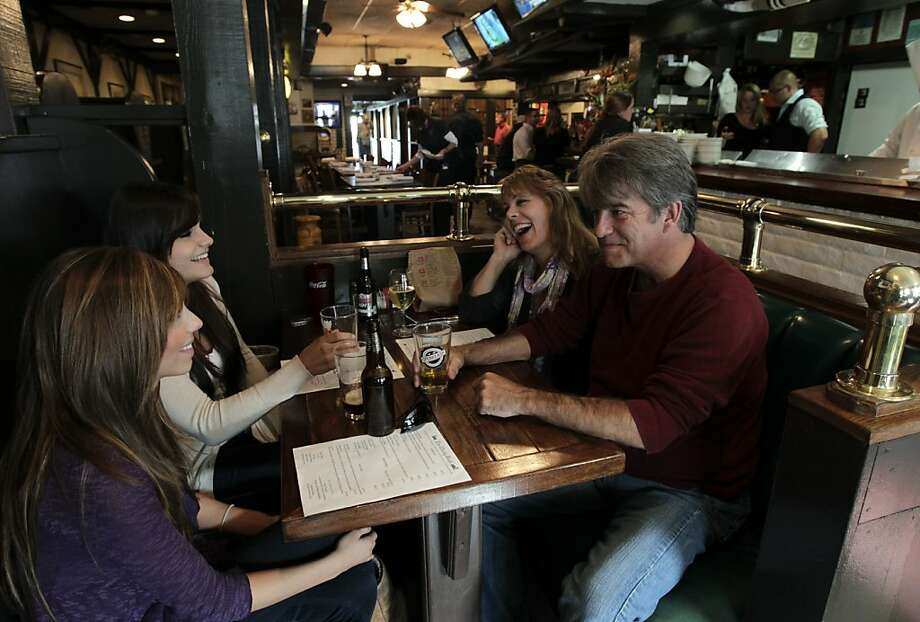 "Barbara Moss and her friend KC Lynch (at right) enjoy pints of cold beer with Moss' daughters Lea and Lauren (at left) at the Mucky Duck restaurant in Monterey, Calif. on Tuesday, August 9, 2011. Lynch, a long-time Monterey resident, recently returned to ""the Duck"" because of its new ownership. Photo: Paul Chinn, The Chronicle"