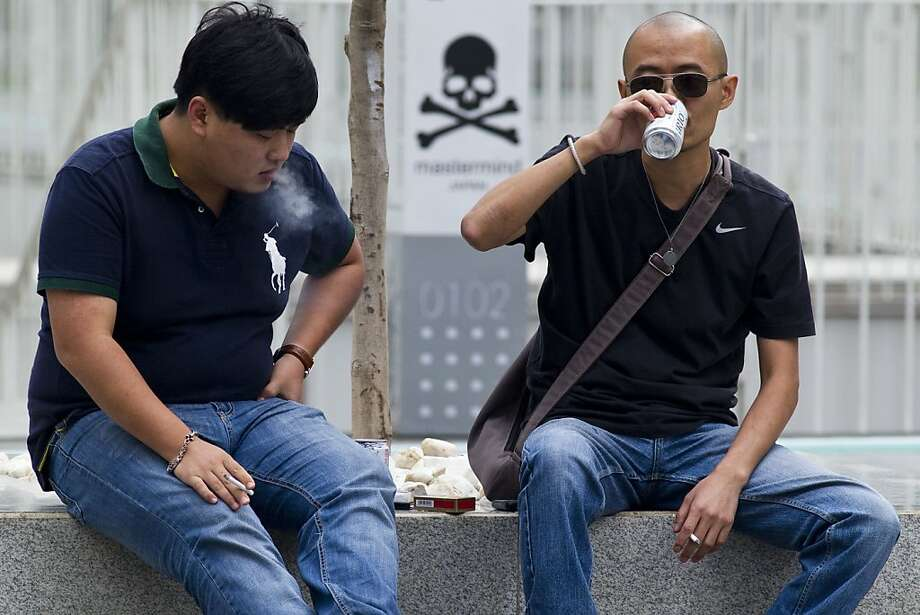 ADVANCE FOR RELEASE THURSDAY, SEPTEMBER 15, 2011, AT 12:01 A.M. EDT - In this Sept. 8, 2011 photo, two men smoke and drink beers during lunch time near a skull and crossbones sign in Beijing's Central Business District, China. Heart disease, cancer, and respiratory disease have replaced hepatitis, diarrhea and malaria as desk work replaces farming, cars replace bicycles, and smoking remains stubbornly popular. (AP Photo/Alexander F. Yuan) Photo: Alexander F. Yuan, AP