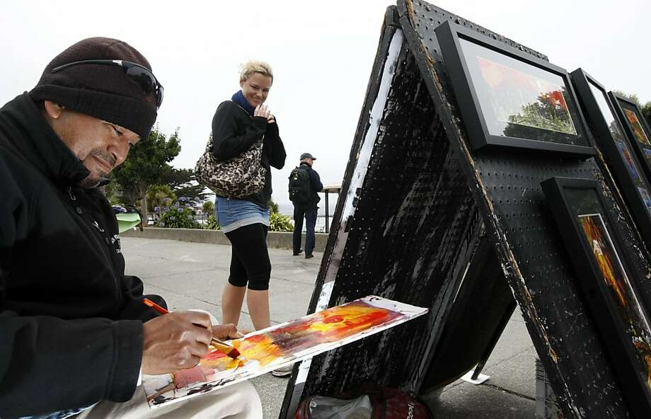 Hayley Stice a tourist from New Zealand looks over Eduardo Guzman, as he creates a painting at his sidewalk stand on Beach Street in San Francisco Fisherman's Wharf area between Hyde and Larkin streets Wednesday September 14, 2011. Photo: Lance Iversen, The Chronicle
