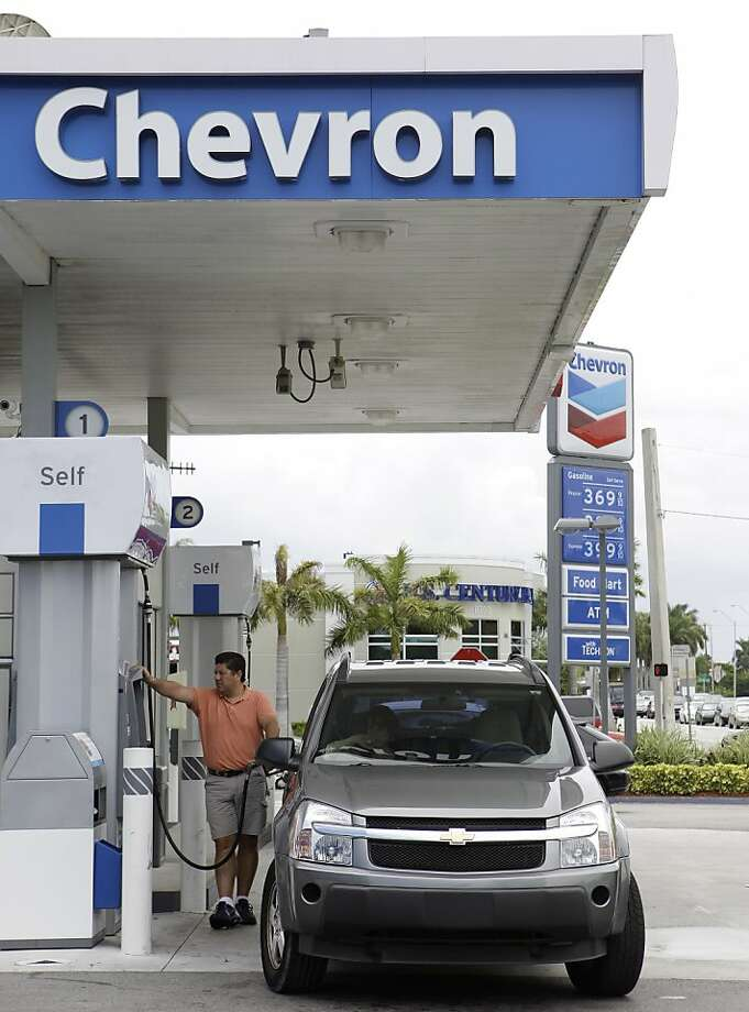 In this photo taken July 26, 2011, a man fuels his car at a Chevron gas station in Miami. The economy slowed in the first six months of 2011 to its weakest pace since the recession ended. High gas prices and scant income gains forced Americans to sharply pull back on spending.  (AP Photo/Lynne Sladky)  Ran on: 07-30-2011 At this Chevron station in Miami, gas is selling for $3.69 per gallon. Higher fuel prices have helped oil companies post hefty profits.   Ran on: 09-16-2011 Chevron has sold its 20 percent share of an offshore site in Brazil. Ran on: 09-16-2011 Chevron has sold its 20 percent share of an offshore site in Brazil. Photo: Lynne Sladky, AP