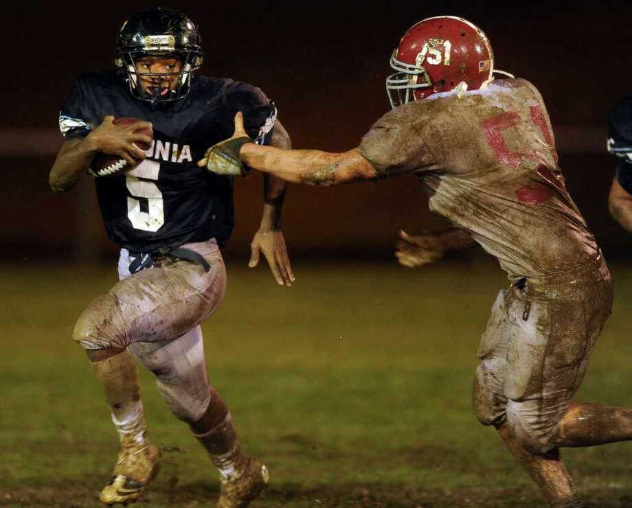 Ansonia High School's Jaiquan McKnight carries the ball as Bethel High School's Peter Serencsics tries to pull him down Tuesday, Nov. 29, 2011 during the Class M Football quarterfinal at Nolan Field in Ansonia, Conn. Photo: Autumn Driscoll / Connecticut Post
