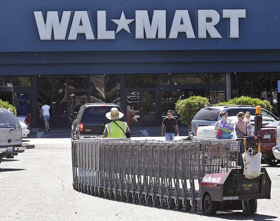 A Wal-Mart worker pull carts at a Wal-Mart store in Pittsburg Calif., Monday, June 20, 2011. A worker at this Wal-Mart was involved in a sex discrimination lawsuit against Wal-Mart. The Supreme Court on Monday blocked a massive sex discrimination lawsuit against Wal-Mart on behalf of women who work there. The court ruled unanimously that the lawsuit against Wal-Mart Stores Inc. cannot proceed as a class action, reversing a decision by the 9th U.S. Circuit Court of Appeals in San Francisco. The lawsuit could have involved up to 1.6 million women, with Wal-Mart facing potentially billions of dollars in damages. (AP Photo/Paul Sakuma)  Ran on: 06-26-2011 A worker pulls carts at a Walmart store in Pittsburg.    Ran on: 08-15-2011 Banks demand that the Consumer Financial Protection Bureau regulate Walmart's finance services. Ran on: 08-15-2011 Banks demand that the Consumer Financial Protection Bureau regulate Walmart's finance services. Photo: Paul Sakuma, AP