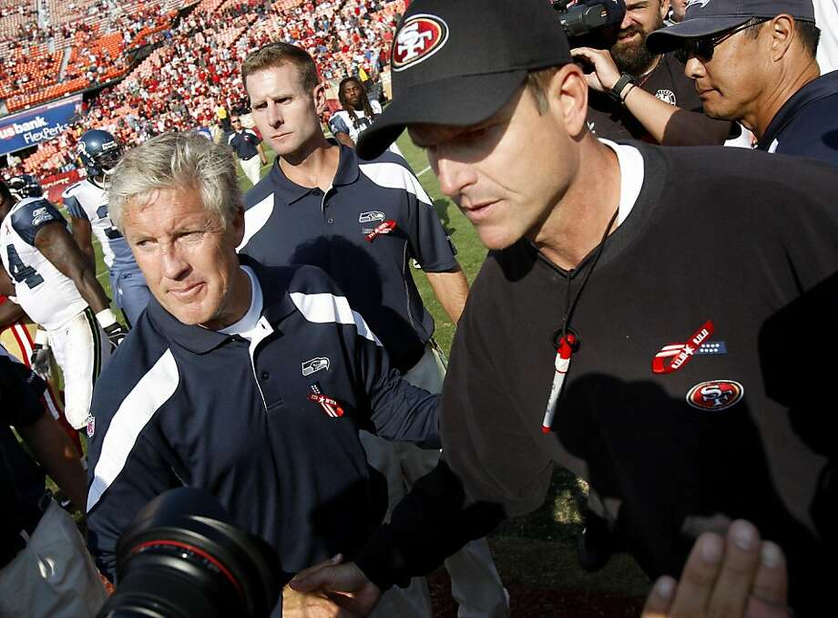 Seahawks coach Pete Carroll (left) and 49ers coach Jim Harbaugh meet at midfield after the game. The San Francisco 49ers defeat the Seattle Seahawks 33-17 at Candlestick Park Sunday September 11, 2011.  Ran on: 09-12-2011 Seahawks coach Pete Carroll and 49ers coach Jim Harbaugh avoided any drama when they met at midfield after the game. Photo: Brant Ward, The Chronicle