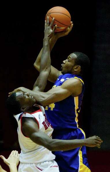 UH forward Alandise Harris, left, blocks a shot by LSU forward Storm Warren during the first half.