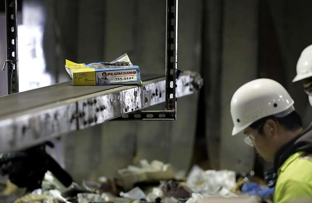 Jason Naraja, a worker of Recycle Central sorts out the phonebooks from the  other recycling