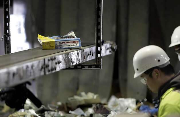 Jason Naraja, a worker of Recycle Central sorts out the phonebooks from the other recycling and places them on a separate conveyor belt, Monday January 31, 2011, in San Francisco, Calif.  Ran on: 02-01-2011 Robert Reed, top, of Recycle Central can find plenty of phone books among the piles of recyclables. Jason Naraja, above, moves them onto a separate conveyor belt. Ran on: 02-01-2011 Robert Reed, top, of Recycle Central can find plenty of phone books among the piles of recyclables. Jason Naraja, above, moves them onto a separate conveyor belt. Photo: Lacy Atkins, The Chronicle
