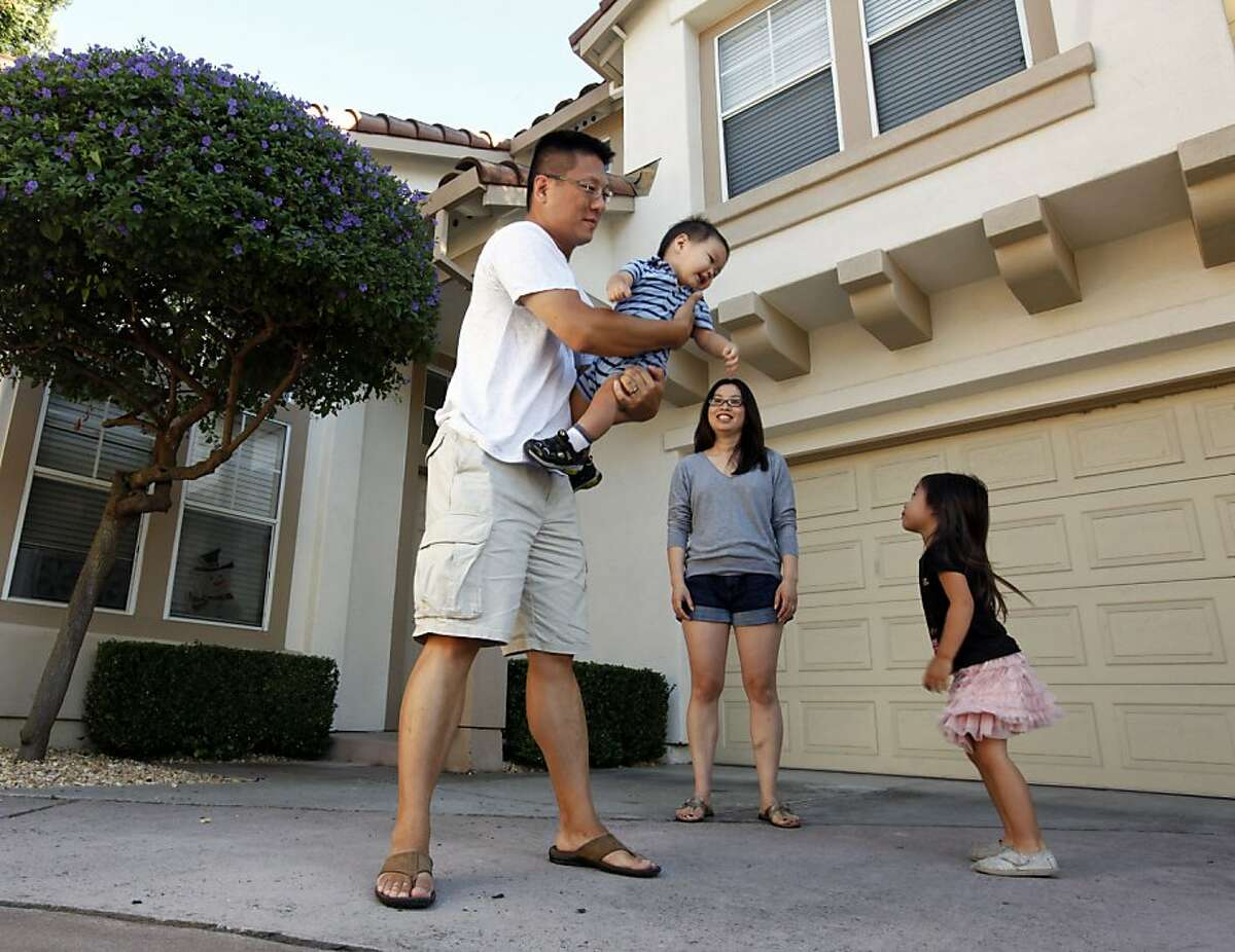 Kit and Miki Wetzler play with their two children Mia age 3 and Jason age 1 in the front courtyard of their Sunnyvale home Thursday August 25, 2011. The couple was shocked when they opened their annual tax assessment bill and saw that Santa Clara County said their property value had jumped $150,000 in just a year. Assessors who downgraded property values during the real estate downturn are now starting to restore them in some instances, saying the market is recovering, but homeowners including the Wetzler say it's not possible their homes are worth that much.