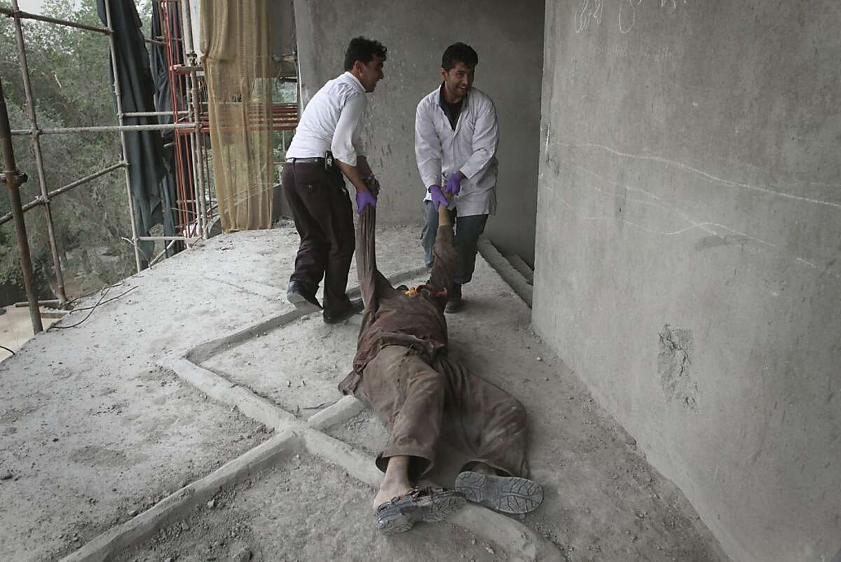 Afghan medics remove the body of a Taliban militant from the building in Kabul, Afghanistan Wednesday Sept. 14,2011. The Afghan government says the two-day insurgent assault in the heart of Kabul has ended and all the attackers have been killed. (AP Photo/Musadeq Sadeq)