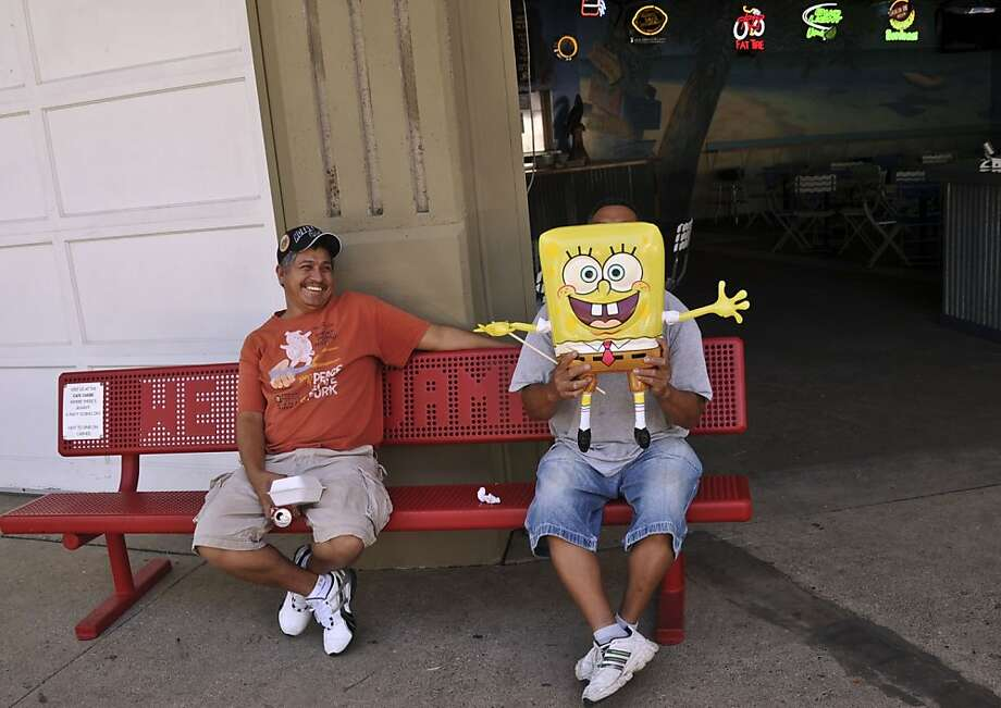Albert Martinez laughs at his friend Roy Trejo who holds a Sponge Bob balloon in front of his face in Falcon Heights, Minn. The two run a small Souvenir  shop and were getting ready for the Minnesota State Fair, on Wednesday, Aug. 24, 2011. (AP Photo/Star Tribune, Richard Sennott) Photo: Richard Sennott, AP