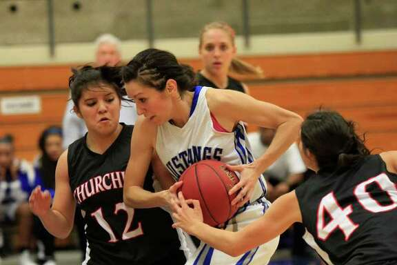 Jay's Ashley Mandujano cuts through the Churchill defense of Mikki Flores (left) and Rebecca Flores.