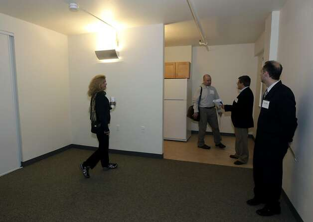 Invited guests tour an available apartment unit at a re-opening ceremony for a Tenderloin apartment building on Eddy Street in San Francisco, Calif. on Wednesday, Sept. 14, 2011. The renovated buildings at 165 Turk Street and 249 Eddy Street will provide 82 homes for low-income seniors in a project spearheaded by the Tenderloin Neighborhood Redevelopment Corp. A lottery was held to determine about half of the tenants, all of which pay only 30% of their income for rent. Photo: Paul Chinn, The Chronicle