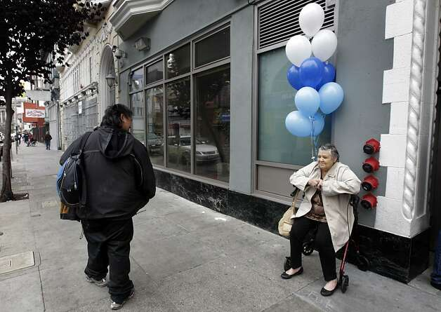 A Tenderloin local walks past a new resident of a renovated Turk Street apartment building in San Francisco, Calif. on Wednesday, Sept. 14, 2011. Two renovated buildings at 165 Turk Street and 249 Eddy Street will provide 82 homes for low-income seniors in a project spearheaded by the Tenderloin Neighborhood Redevelopment Corp. Photo: Paul Chinn, The Chronicle
