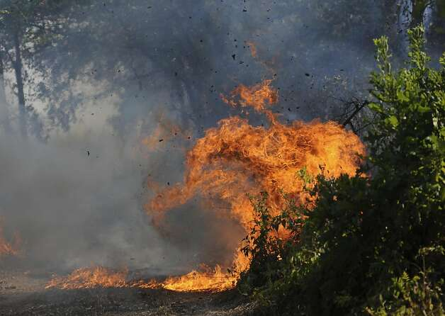 A fire burns in the wooded lots west of Hawk Road Saturday, Sept. 10, 2011 near Diana, Texas. Texas is in the midst of one of its worst wildfire outbreaks in state history. A perilous mix of hot temperatures, strong winds and a historic drought spawned the Bastrop-area fire, the largest of the nearly 190 wildfires the state forest service says erupted this week, killing four people, destroying more than 1,700 homes and forcing thousands to evacuate.  (AP Photo/The Tyler Morning Telegraph, Sarah A. Miller) Photo: Sarah A. Miller, AP