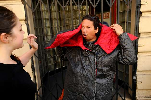 Abel Hernandez tries on a wearable sleeping bag prototype made by Veronika Scott, left, on Friday, Sept. 9, 2011, in San Francisco. Scott hopes her coats, which are made of Tyvek and convert to sleeping bags, will help homeless people. Photo: Noah Berger, Special To The Chronicle