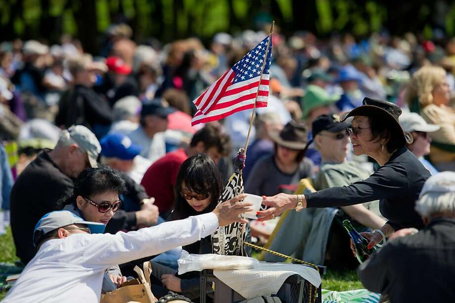 Marie Lee, right passes a drink to a friend as they enjoy the San Francisco Opera in the Park  performance in Golden Gate Park on September 11, 2011 in San Francisco, Calif. Photo: David Paul Morris, Special To The Chronicle