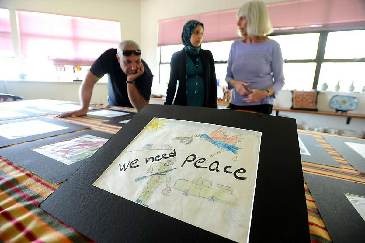 Staff members at the Middle East Children's Alliance (MECA) look over artwork by Palestinian youths on Friday, Sept. 9, 2011, in Berkeley, Calif. From right to left are founder Barbara Lubin, communications coordinator Leena Al-Arian and associate director Ziad Abbas.