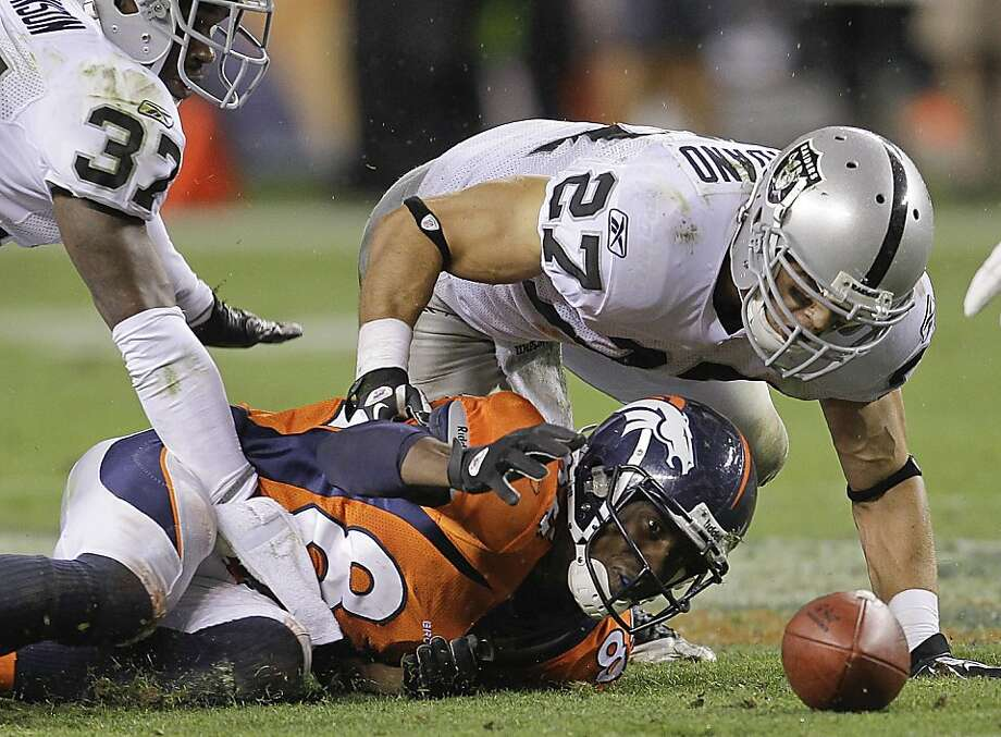 Denver Broncos wide receiver Brandon Lloyd (84), Oakland Raiders defensive back Matt Giordano (27) and defensive back Chris Johnson (37) reach for the ball that Lloyd fumbled in the fourth quarter an NFL football game, Monday, Sept. 12, 2011, in Denver. The Raiders won 23-20. (AP Photo/Joe Mahoney) Photo: Joe Mahoney, AP