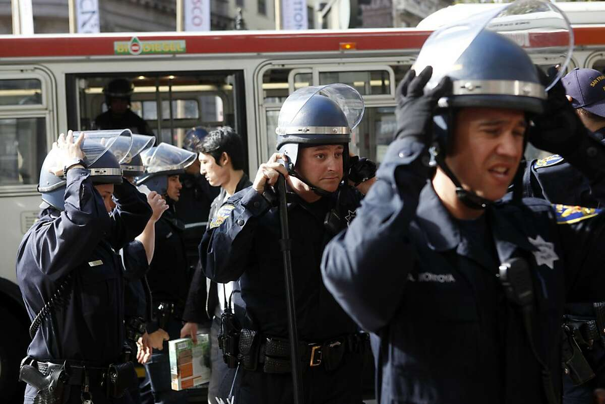 San Francisco Police officers don helmets before closing down the Powell Street BART and MUNI station following a protest involving free speech in the ticket area of the station on Thursday, September 8, 2011 in San Francisco, Calif.