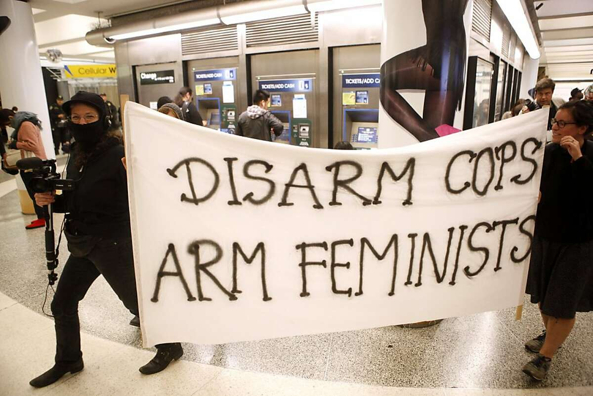 """Protesters carry a banner depicting """"Disarm Cops, Arm Feminists"""" during a protest in the Powell Street BART and MUNI station on Thursday, September 8, 2011 in San Francisco, Calif."""
