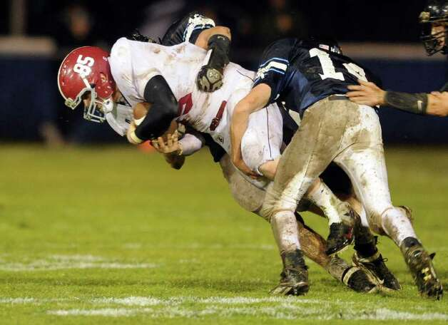 Bethel High School's Calvin Daniels is brought down by Ansonia's Tyler Wood and #14 Ryan O'Connol Nov. 29, 2011 during the Class M Football quarterfinal at Nolan Field in Ansonia, Conn. Photo: Autumn Driscoll / Connecticut Post