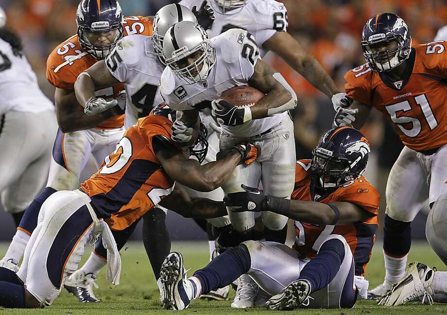 Oakland Raiders running back Darren McFadden (20) tries to break a tackle by Denver Broncos linebacker Mario Haggan (57) adn Denver Broncos defensive back Brian Dawkins (20) in the third quarter of an NFL football game, Monday, Sept. 12, 2011, in Denver.  (AP Photo/Joe Mahoney) Photo: Joe Mahoney, AP