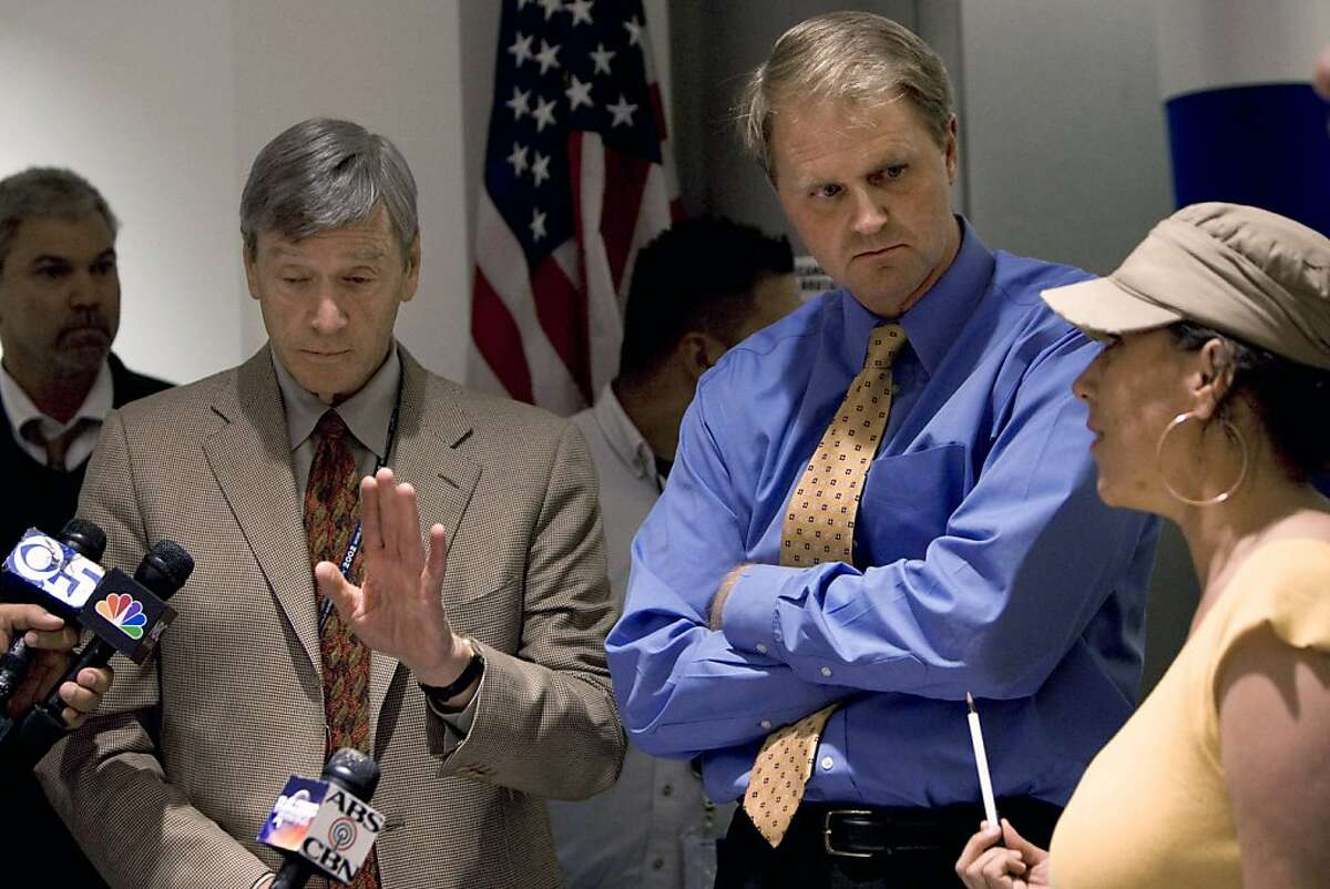 Larry Pitts (left) and Nathan Brostrom speak with protesters including Marika Goodrich (right) at the University of California offices in Oakland, Calif., on Monday, Nov. 23, 2009. The protesters came into the offices asking to speak with President Mark Yudof and Pitts and Brostrom agreed to come down and answer questions.