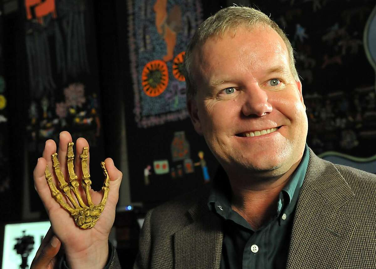 Professor Lee Berger, an American who is a professor at South Africa's University of the Witwatersrand, poses with the reconstructed hand of a hominin he discovered, during the unveiling of this Sediba Fossil in Johannesburg, on September 8, 2011. Until now, the first tool-maker was widely believed to be Homo habilis, based on a set of 21 fossilized hand bones found in Tanzania that date back 1.75 million years. However, a close examination of two partial fossilized skeletons of Au. sediba discovered in South Africa in 2008 and the new Sediba Fossil discovery suggest that these creatures who roamed the Earth 1.9 million years ago were crafting tools even earlier, and could be the first direct ancestor of the Homo species. AFP PHOTO / ALEXANDER JOE (Photo credit should read ALEXANDER JOE/AFP/Getty Images)