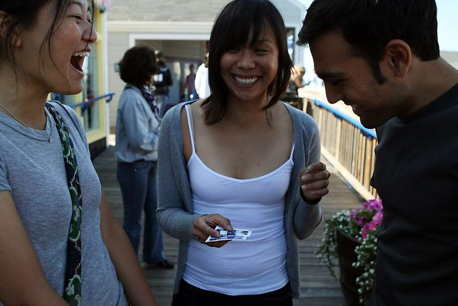 Joanne Lue, left, Myra Zheng, and Sam Hashemi laugh after Zheng mistook Hashemi for another person in her picture during a game of Assassins at Pier 39 on July 10, 2011. Undercover Street Games is an informal group of people that gather every now and then to play a sort of childhood playground type game in an urban environment. Photo: Maddie McGarvey, The Chronicle