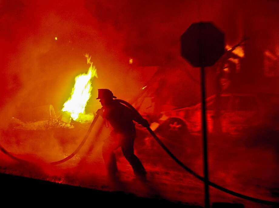 A firefighter helps battle the fire that was caused by an explosion from a gas line rupture. Photo: Noah Berger, The San Francisco Chronicle