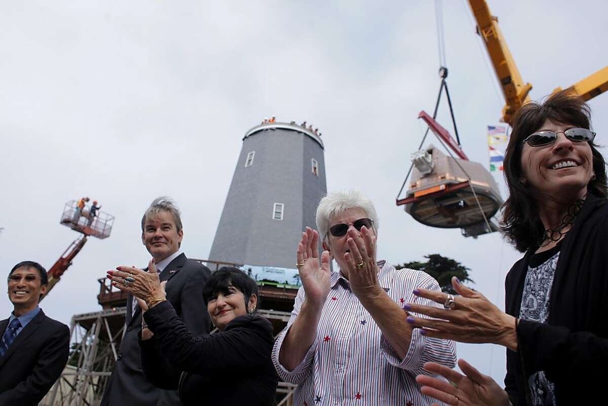 San Francisco Supervisor Eric Mar, left, Consul General for the Netherlands in San Francisco, Bart van Bolhuis, Hendrika Neys, Marista Henneberque, and Natasha Yankoffski, clap as the 64 ton copper windmill dome is lifted and placed on top of the Samuel Murphy Windmill, Monday September 12, 2011 in Golden Gate Park in San Francisco, Calif.