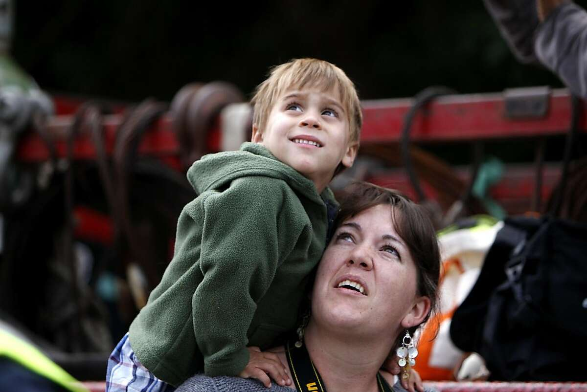 """Colton Barbeua, climbs on his nanny Kerry Connelly as they watch the raising of a 64 ton copper windmill dome and it being placed on top of the Samuel Murphy Windmill, Monday September 12, 2011 in Golden Gate Park in San Francisco, Calif. Connelly said, """" My father , who died a year ago, use to play here when he was a kid and when they shut it down in 1935 he was heart broken. He would be on cloud nine if he was here."""""""