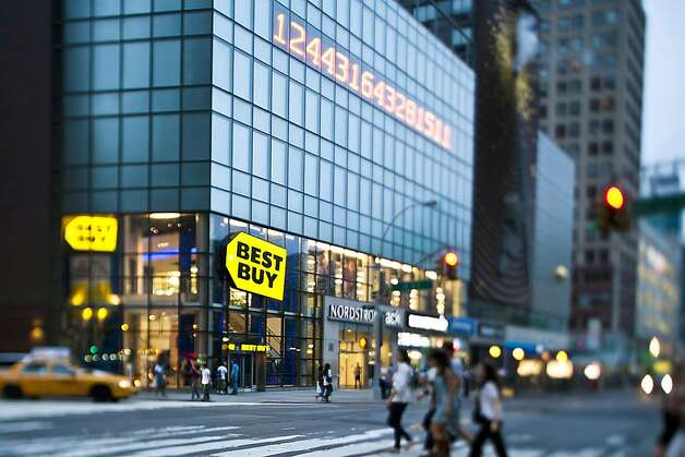 Pedestrians pass in front of a Best Buy Co. store in this photo taken with a tilt-shift lens in New York, U.S., on Sunday, June 12, 2011. Best Buy Co., the world's largest consumer electronics retailer, is scheduled to announce quarterly earnings on June 14 before the opening of U.S. financial markets. Photographer: Chris Goodney/Bloomberg  Ran on: 06-15-2011 Best Buy is adjusting as items like flat-screen televisions and DVDs no longer sell as well as they once did. Photo: Chris Goodney, Bloomberg