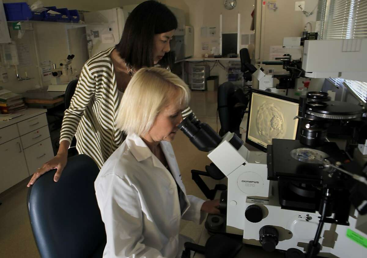 Dr. Mylene Yao, standing, and Dr. Lynn Westphal look over an embryo in Endocrinology and Infertility Clinic, Monday Aug. 2, 2010, in Stanford, Calif. Ran on: 08-23-2010 Dr. Mylene Yao (left) developed a test that predicts a womans in vitro fertilization odds with clinical data from Dr. Lynn Westphal at Stanfords Reproductive Endocrinology and Infertility Center.