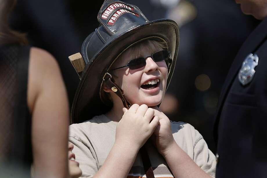 9-year-old Jack Stanfield wears his father's fire helmet, who is a firefighter with engine 38 in San Francisco, during the ceremony as the members of the San Francisco Police and Fire departments commemorate the the 10th anniversary of September 11, 2001 attacks, at a ceremony at Civic Center Plaza in San Francisco, Ca. on Saturday September 10, 2011. Photo: Michael Macor, The Chronicle