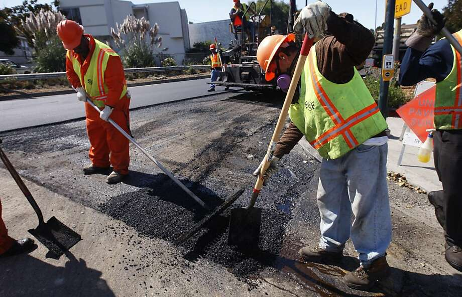 A Department of Public Works crew smoothes fresh asphalt at a repaving project on an access road leading to southbound Highway 101 and Bayshore Boulevard from Third and Jamestown streets in San Francisco, Calif. on Friday, Sept. 9, 2011. If passed by voters, a bond measure would pour an additional $248 million into repairing city streets, sidewalks and curbs. Photo: Paul Chinn, The Chronicle