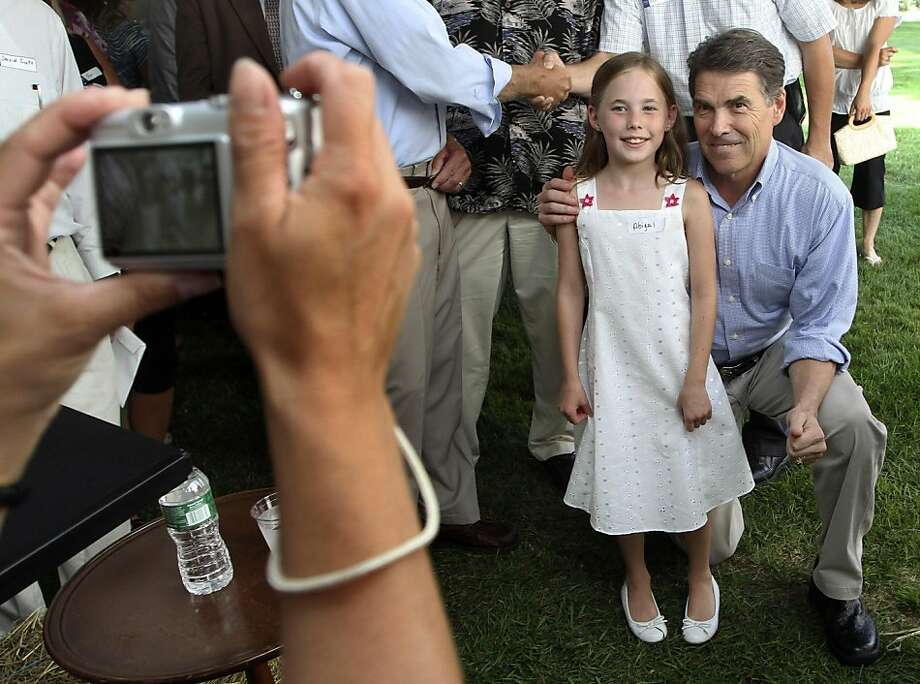 Republican presidential candidate Texas Gov. Rick Perry poses for a photo with guests at a house party, Saturday, Sept. 3, 2011, in Chichester, N.H. (AP Photo/Jim Cole) Photo: Jim Cole, AP