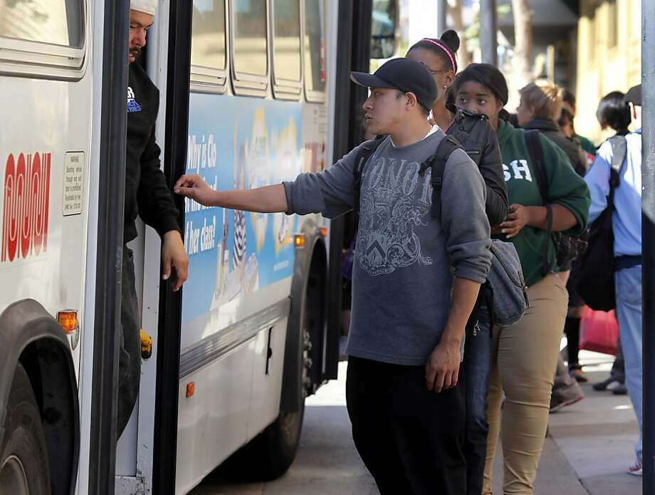 On Van Ness Avenue, some riders use the back door while others use the front to board a 49 bus. The San Francisco MTA will consider legalizing and even encouraging back door boarding of MUNI buses in an effort to speed up transit. Photo: Brant Ward, The Chronicle