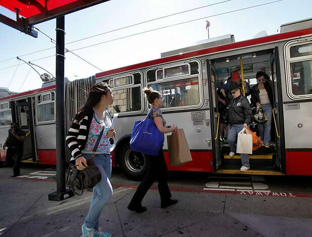 On Van Ness Avenue, riders leave through a rear door while new passengers run to the front. The San Francisco MTA will consider legalizing and even encouraging back door boarding of MUNI buses in an effort to speed up transit. Photo: Brant Ward, The Chronicle