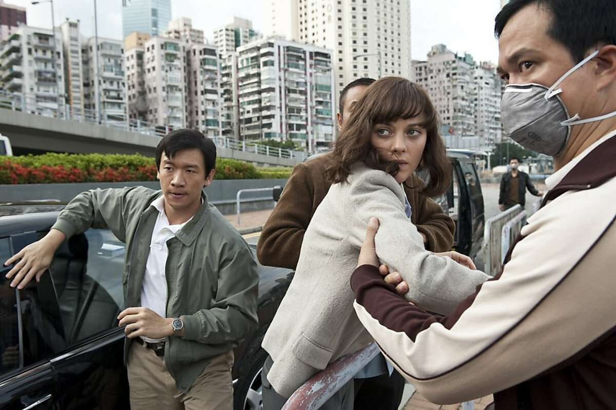 CHIN HAN (left) as Sun Feng and MARION COTILLARD (center) as Dr. Leonora Orantes in the ?'Contagion,?