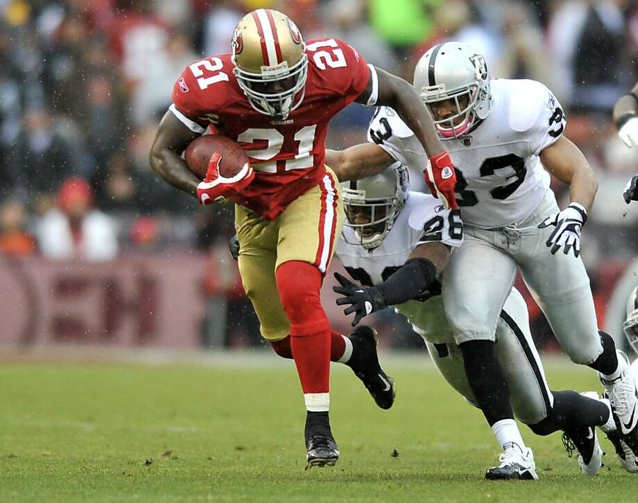 San Francisco's Frank Gore (number 21) breaks away from the pack and rushes for 64 yards as the San Francisco 49ers take on the Oakland Raiders at Candlestick Park on Sunday, October 17, 2010.   Ran on: 10-18-2010 Frank Gore breaks free for 64 yards midway through the fourth quarter, setting up the 49ers' final touchdown. Gore finished with 149 yards on 25 carries. Ran on: 10-18-2010 Frank Gore breaks free for 64 yards midway through the fourth quarter, setting up the 49ers' final touchdown. Gore finished with 149 yards on 25 carries. Photo: Chad Ziemendorf, The Chronicle