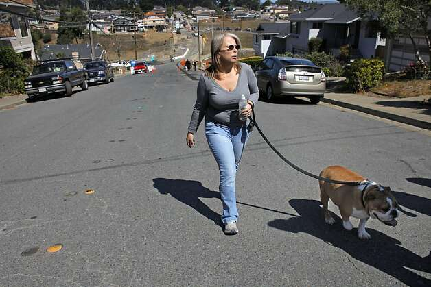 "Resident Tina Pellegrini walks her dog Gus back to the car as they leave the blast site, Tuesday September 6, 2011, in San Bruno, Calif.  Their family home was one of the 38 homes destroyed in the PG&E explosion last September. Having not seen the site from this angle, Tina said, "" when I see that hole and the black burnet tree stumps it bring the whole thing back to me, I just want to be back in my home."" Photo: Lacy Atkins, The Chronicle"